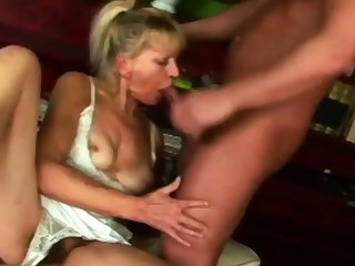 Hot granny is sucking her neighbour's big cock on the couch.